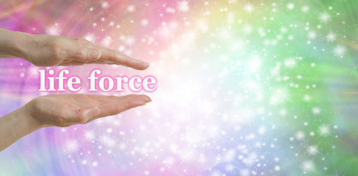 Your Life Force is in Your Hands - Female parallel hands with the words 'life force, floating between surrounded by a sparkles on a pastel rainbow colored  background and plenty of copy space