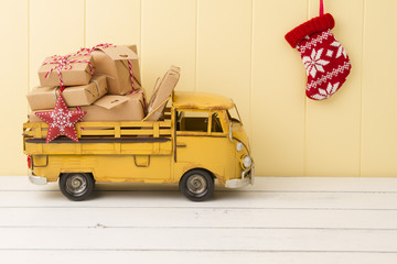Some paper parcels (christmas gift boxes) wrapped with paper kraft and tied with red & white baker's twine in a yellow truck. A christmas sock on the wainscot