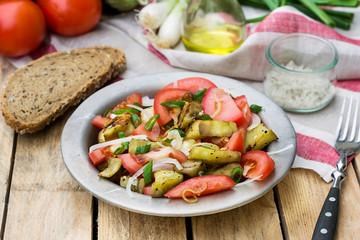 Warm autumn salad with eggplant, tomato, onion