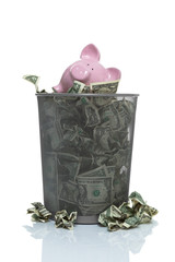 Garbage can full of money spilling over with piggy bank in it