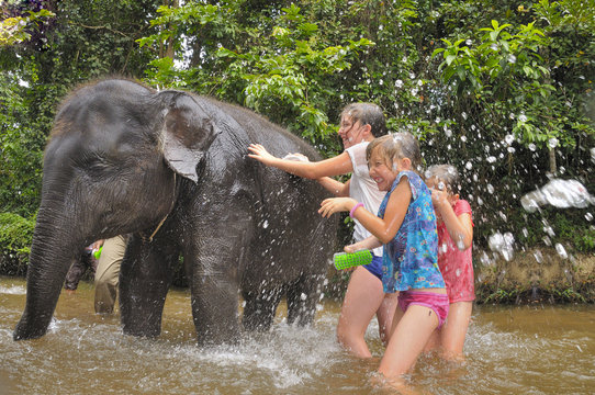 Children bathing a baby elephant in Asia