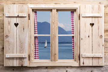 Wooden window with a lake as reflections