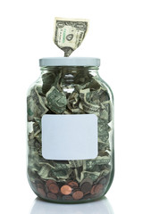 Glass jar full of money with a dollar bill in the top