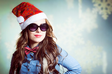 Funny smiling hipster girl in sunglasses wearing santa hat
