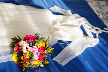 Bride dress and wedding bouquet lie on the bed
