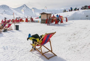 View of man resting on chair in mountains.  Ski resort Livigno.