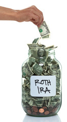 Hand putting money into a savings jar with a white ROTH IRA labe