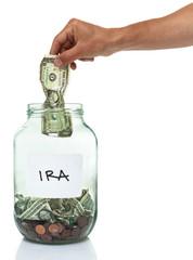 hand putting a dollar bill in an IRA savings jar