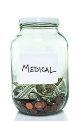 Glass jar with with a white medical label and some money in it