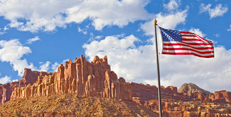 Capitol Reef National Park in Utah, panorama of red rocks and American flag waving on a beautiful summer day with blue sky