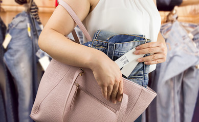 woman steals trousers at the boutique - fototapety na wymiar