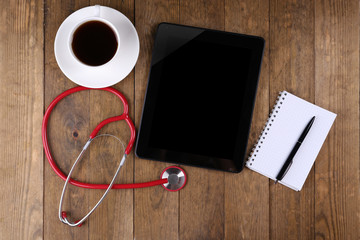 Doctor workplace with blank tablet and stethoscope on wooden background