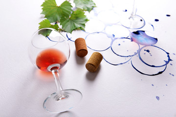 Wine glass and branch of grapes painted with stains of glass on white paper background