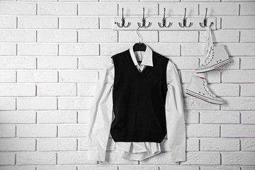 School clothes for boy on hanger, on white wall background