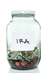 Glass jar with with a white IRA label and some money in it