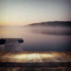 vintage wooden board table in front of abstract photo of misty and foggy lake at morning sunrise.