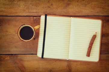 blank open vintage notebook, old paper and wooden pencil next to cup of coffee over wooden table. ready for mockup