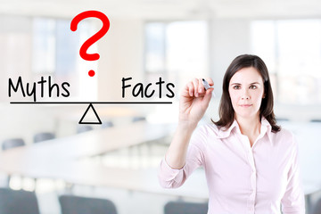 Young business woman writing myths and facts compare on balance bar. Office background.