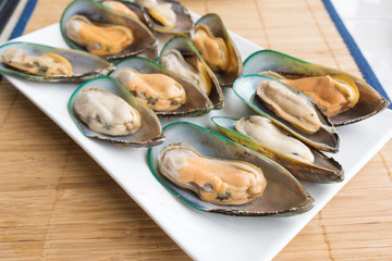 Fresh mussels in white dish on the table
