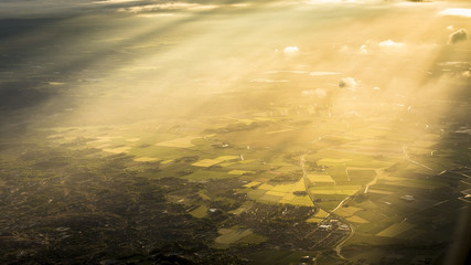 Fields, forest and sunbeam from above