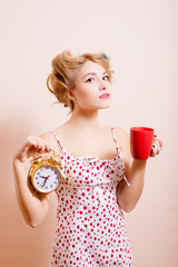 Housewife with alarm-clock and cup