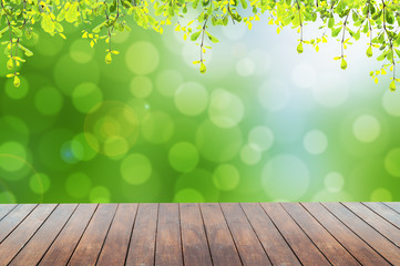 Green leaves with green bokeh and sunlight and wood floor