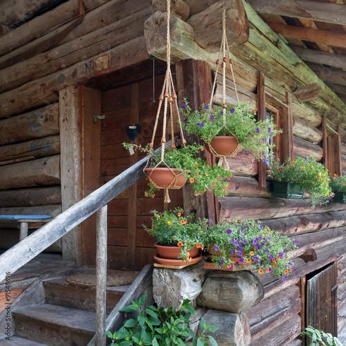 Baita di montagna in legno con fiori e piante immagini e for Case rustiche di montagna