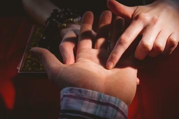 Fortune teller reading mans palm