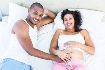 Portrait of pregnant wife with husband lying on bed