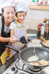 Little asian girl making pancake