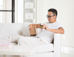 casual asian man online shopping in livingroom
