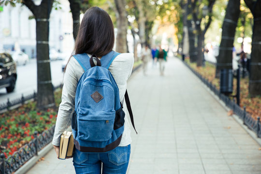 Back view portrait of a female student walking