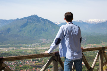 man stands on high terrace looking to mountains and town
