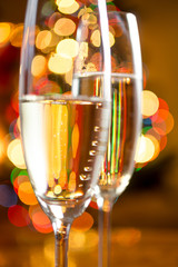 abstract photo of champagne in glasses against colorful lights