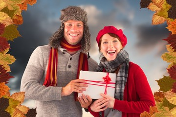 Composite image of couple smiling and holding gift