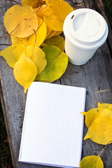 Notebook, cup of coffee and yellow autumn leaves on the old wooden table.