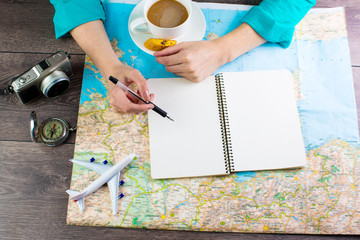 Map traveler. Woman bent over the map in search of a best route for the next vacation time to travel.