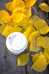 Cup of coffee and yellow autumn leaves on the old wooden table