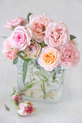 Beautiful fresh pink roses in a vase on a table .light background.