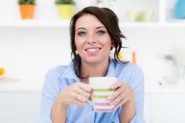 Junge Frau trinkt Kaffee in Küche