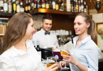 Two girls flirting with barman