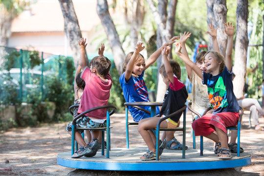 Bambini felici con le mani alzate su una giostra