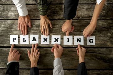 Eight business people assembling the word Planning