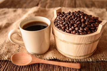 Coffee beans in wooden bowl and coffee cup on wooden background.