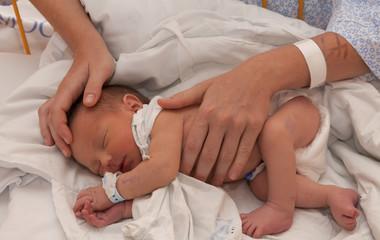 Säugling in den Händen seiner Mutter