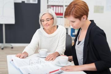 ältere mitarbeiterin hilft einer jüngeren kollegin