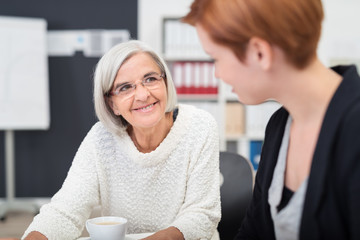 zwei lächelnde kolleginnen verschiedenen alters unterhalten sich am arbeitsplatz