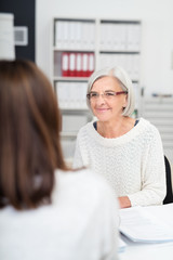 ältere geschäftsfrau unterhält sich mit einer kollegin am schreibtisch