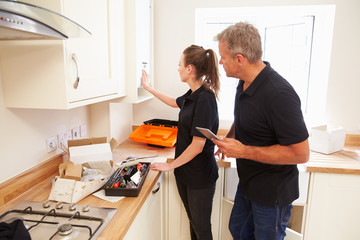 Man and woman working on a new kitchen installation