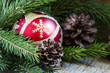 Christmas balls, spruce branches and pine cones on old wooden ba